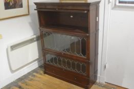 A Chapter Simpoles mahogany four section bookcase with three leaded up and over glass doors (top
