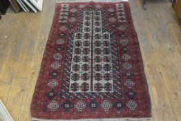 An Afghan prayer rug, the shaped panel with stylised leaf design enclosed within a multiple