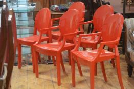 A set of four plus one moulded red acrylic open arm dining/side chairs with oval backs, raised on