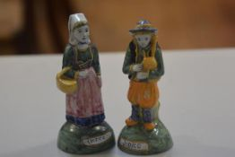 A pair of Quimper figures, a Man with Bagpipes and a Woman with Shopping Basket, decorated with