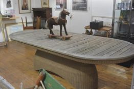 A large stylish garden table with hardwood slatted top with rounded angles on shaped recycled