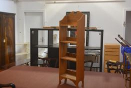A neat Edwardian oak upright open bookcase, the broken pediment above four shelves, with shaped side
