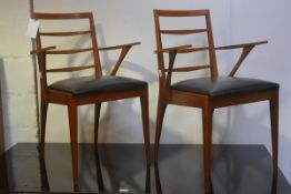 A pair of mid century teak ladderback open carver chairs with original vinyl seats, raised on turned