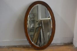 A 1920s oak oval bead and dart bevelled frame wall mirror (88cm x 49cm)