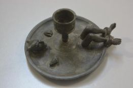 A novelty pewter candlestick with crushed Devil with shackled feet to circular base (missing handle)
