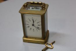 A French four glass brass clock with enamelled dial and roman and arabic numerals, complete with key