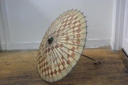 A Japanese parasol with bamboo handle and paper shade decorated with handpainted stylised leaves