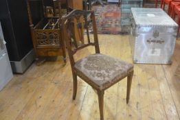 An Edwardian walnut side chair in the Adam taste with harebell and pedimented carved top, with