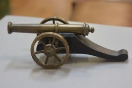 A treen gun carriage mounted with brass wheels and miniature canon (h. 8cm x l.25cm)