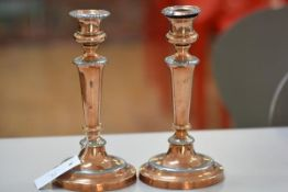 A pair of 19thc copper and pewter mounted baluster stem candlesticks on circular moulded bases, with