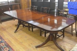 A reproduction mahogany twin pedestal extending dining table, the rectangular top with rounded