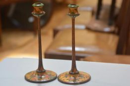 A pair of treen carved naively painted 1920s candlesticks, raised on circular moulded bases (h. 26cm