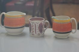 A Susie Cooper for Gray's Pottery handpainted pair of milk jugs with yellow, orange and black banded