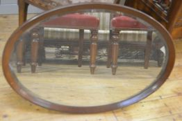 An Edwardian mahogany oval framed wall mirror with bevelled glass plate (l. 78cm x 53cm)