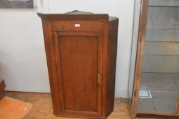 A George III oak hanging corner cupboard, with single panelled door (section of cornice missing).