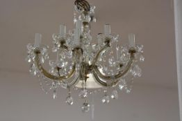 A George III style ten-light cut-glass chandelier, suspending prismatic drops, with brass rose and