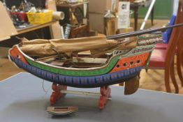 A painted wooden model of a Chinese junk, brightly decorated with tiller, masts anchor etc (losses).