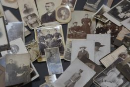 A group of unframed early 20th century sepia and black and white portrait photographs.