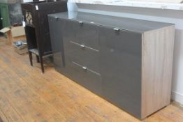 A modern grey toughened glass topped and fronted oak veneered side cabinet fitted with a central