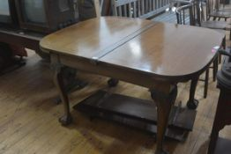 A George III style mahogany drawleaf dining table, early 20th century, the rectagular top with bowed