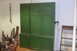 A late 19th century green-painted country bookcase cabinet, the upper section with three panelled