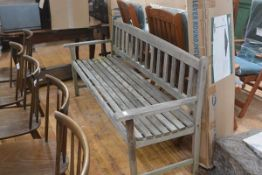 A weathered slatted garden bench. Length 172cm