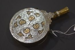 A late 19th century white metal and brass powder flask, probably Turkish, circular, with engraved