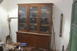 A mid-Victorian oak bookcase cabinet, the moulded cornice over three glazed doors enclosing