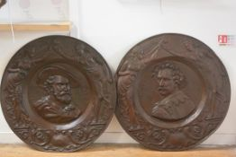 A pair of unusually large commemorative patinated metal roundels, one in relief with an image of