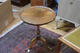 A walnut pedestal wine table on turned column and tripod support (top a/f). 52cm by 40cm diameter