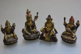 A group of four bronze deities with painted decoration sitting on lotus leaf and throne (tallest