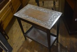 An Edwardian Arts & Crafts two tier occasional table, the top with scrolling leaf border, on