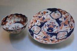 A Japanese Imari style plaque decorated with traditional vases, flowers etc., and a similar