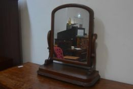 A Victorian mahogany swing mirror with arch top on S-scroll supports and plinth base. 61cm by 54cm
