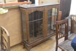 A 1920's mahogany display cabinet, with twin glazed doors and glass shelved interior, on shell