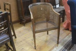 A walnut bergere chair, early 20th century, on square tapered legs with spade feet. 83cm high