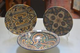 Two Moroccan style plates decorated with traditional scrolls, flowers, symbols etc., (d.29cm) and