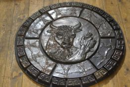 A pottery glazed circular plaque of Theseus and the Minotaur with a border of dancing figures and