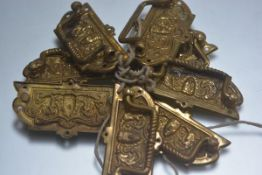 A set of eight 19th century embossed brass bale handles with mask panels. Each 4.5cm by 9cm