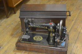 A Singer sewing machine model F1074898, complete with fittings and cover (a/f) 32cm by 50cm by 28cm