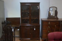 A reproduction mahogany two part bookcase with dentil cornice, twin glazed doors over two drawers