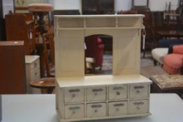 A 19thc treen child's dresser with painted finish in cream, fitted plate rack back and open