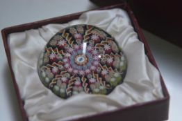 A Perthshire paperweight with millefiori canework decoration, with original box. 6.5cm diameter