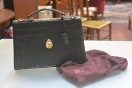 A Mulberry briefcase in embossed crocodile effect black leather, with loop handle to top and brass