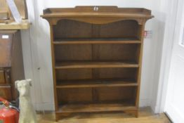 An Edwardian Arts & Crafts upright open bookcase, with rectangular top and pierced ledge back and