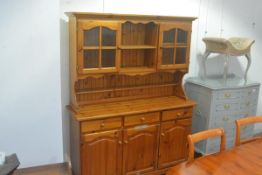 A modern pine two part kitchen dresser, the central shelves flanked by glazed panel doors and a