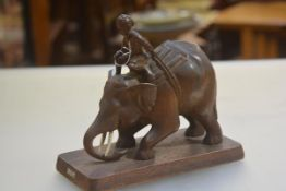 A Burmese carved wood figure of a Boy Riding an Elephant, with plaque (h.22cm x 25cm x 12cm)