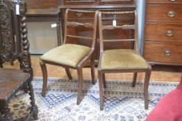 A pair of Regency mahogany dining chairs, with carved rail backs, on sabre legs (one leg a/f).