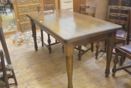 An oak rectangular dining table with moulded edge on turned legs. 76cm by 159cm by 79cm