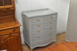 A vintage French green painted and gilt serpentine ledge back chest of drawers, with five long